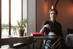 Picture of pretty young woman sitting at the table near book in cafe and looking at camera while drinking coffee.