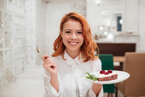 Picture of redhead young happy woman eating cake in cafe. Looking at the camera.