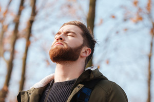 Picture of relaxed serious bearded young man standing in the forest with eyes closed.