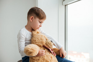 Picture of sad boy near window with teddy bear waiting for parents at home. Look aside.