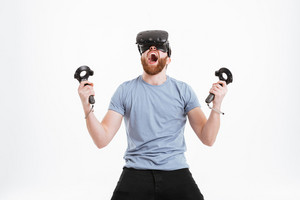 Picture of screaming emotional bearded man wearing virtual reality device standing over white background.