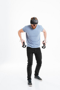 Picture of screaming young bearded man wearing virtual reality device standing over white background while holding joysticks in hands.
