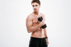 Picture of serious sportsman standing with dumbbell in gym over white background.