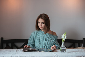 Picture of serious young lady sitting at the table in cafe and reading magazine.