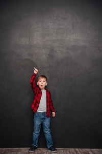 Picture of shocked little boy standing over chalkboard and pointing up. Looking at camera.