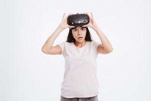Picture of shocked young lady wearing virtual reality device over white background.