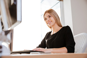 Picture of smiling young lady worker sitting in office near computer while typing. Looking at computer.