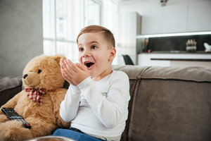 Picture of surprised boy on sofa with teddy bear at home watching TV while eating chips.