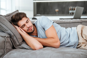 Picture of tired man sleeping on a sofa. Eyes closed.