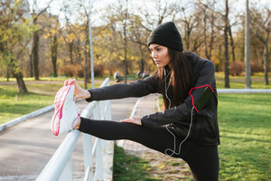 Picture of woman runner in warm clothes and headphones in autumn park make sport exercise