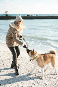 Picture of young attractive caucasian lady walks in winter beach with dog on a leash.