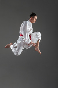 Picture of young attractive sportsman dressed in kimono practice in karate isolated over grey background. Looking aside.