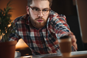 Picture of young bearded designer dressed in shirt in a cage and wearing glasses working with project late at night and tries to take cup of coffee