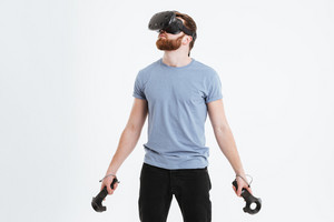 Picture of young bearded man wearing virtual reality device standing over white background while holding joysticks in hands.