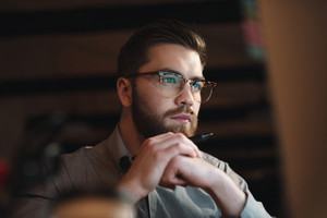 Picture of young bearded web designer dressed in shirt and wearing eyeglasses working late at night and looking at computer. Holding pen.