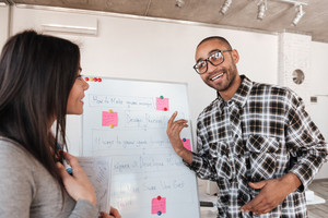 Picture of young cheerful business couple in office working with flipchart. Look at each other.