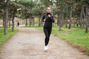 Picture of young cheerful lady runner in warm clothes and earphones running in autumn park