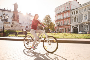 Picture of young cheerful woman dressed in sweater walking with her bicycle in the city.