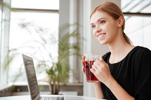 Picture of young cheerful woman worker sitting in office while using laptop computer and drinking hot tea. Looking aside.