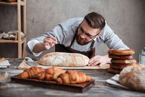 Picture of young concentrated man baker standing at bakery near bread. Looking aside.