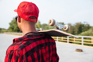 Picture of young dark skinned guy holding skateboard. Against the nature background.