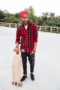Picture of young dark skinned guy wearing cap holding his skateboard. Against the nature background.