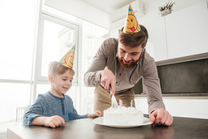Picture of young father cutting the birthday cake of his little son.