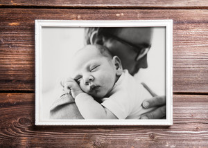 Picture of young father holding his newborn baby son in his arms. Fathers day concept. Studio shot on wooden background.
