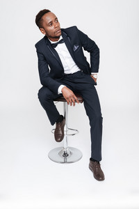 Picture of young handsome african businessman posing in studio and sitting. Isolated over white background. Look aside.