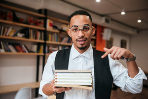 Picture of young handsome african businessman wearing eyeglasses standing in library while holding notebooks. Look at camera and pointing.