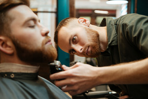 Picture of young handsome man getting beard haircut by bearded hairdresser while sitting in chair at barbershop. Focus on hairdresser.