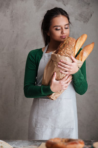 Picture of young happy lady baker standing and holding bread. Looking aside.
