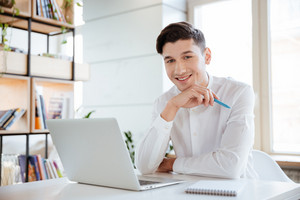 Picture of young happy man dressed in white shirt using laptop computer. Coworking. Looking at camera.