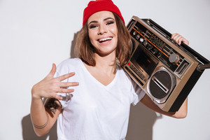 Picture of young happy woman dressed in white t-shirt standing isolated over white background while holding tape recorder.
