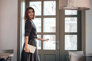 Picture of young incredible cute lady open the door in cafe and holding book.