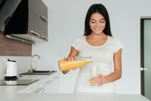 Picture of young lady with glass of juice standing in the kitchen. Look at juice and smile.