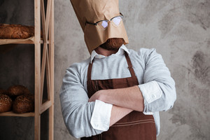 Picture of young man baker standing with paper bag on head wearing glasses at bakery near bread.