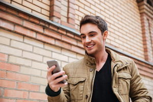Picture of young man walking on the street and chatting by his phone outdoors. Look at phone.