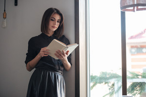 Picture of young pretty lady standing near window in cafe and reading book.
