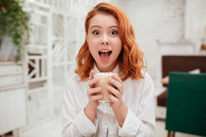 Picture of young redhead surprised happy woman drinking coffee in cafe. Looking at the camera.