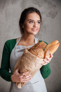 Picture of young smiling lady baker standing and holding bread. Looking aside.