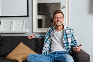 Picture of young smiling man dressed in shirt in a cage print sitting on sofa in home and looking at camera while chatting by phone.
