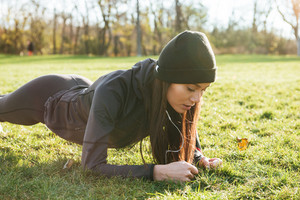 Picture of young sport lady in warm clothes and headphones in autumn park make plank
