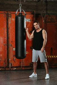 Picture of young strong boxer standing in a gym near punch bag. Looking at camera.