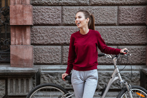 Picture of young woman dressed in sweater walking with her bicycle in the city while standing near wall and laughing. Look aside.