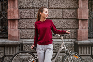 Picture of young woman dressed in sweater walking with her bicycle in the city while standing near wall. Look aside.