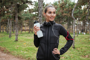 Picture of young woman runner in warm clothes and headphones looking aside in autumn park while holding bottle of water