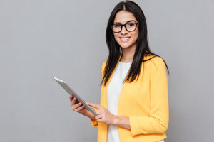 Picture of young woman wearing eyeglasses and dressed in yellow jacket holding tablet computer over grey background. Look at camera.