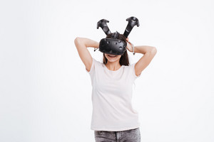 Picture of young woman wearing virtual reality device while holding joystick over white background.