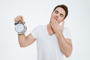 Picture of young yawning man dressed in white t-shirt standing over white background showing alarm to camera.